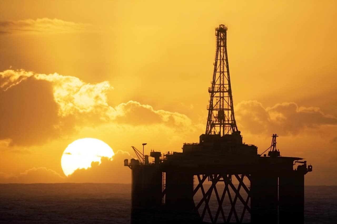 Sun rising behind an oil rig. Drillers.com