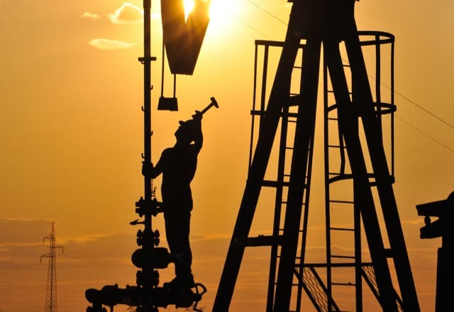 amazing facts about the oil industry illustration - Oilfield worker on a rig at sunset