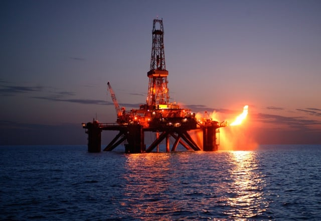 Gas Rig flaring at sunset off the coast of Ireland, illustrating oil and gas industry jobs article